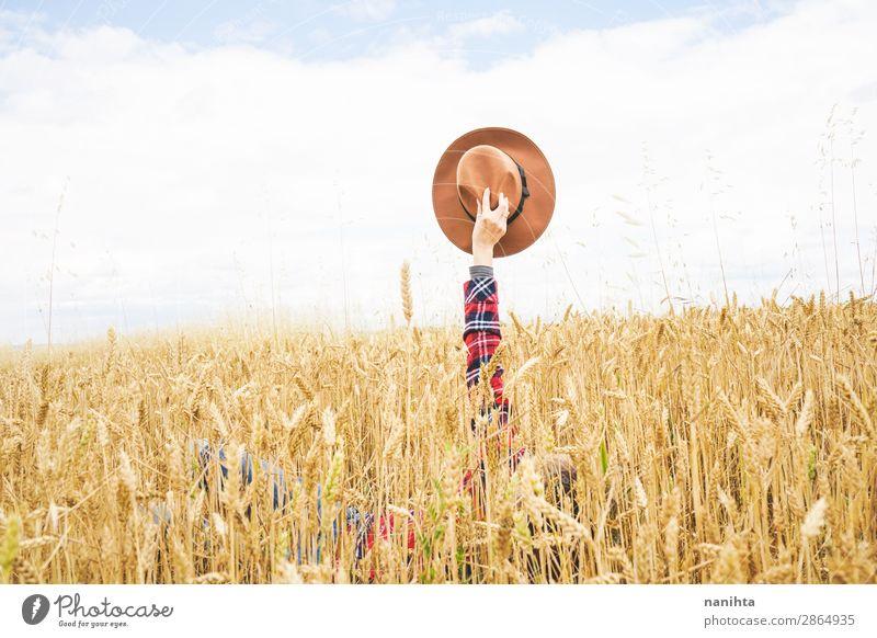 Hand hält einen Cowboyhut über einem Weizenfeld. Bioprodukte Lifestyle Stil Design Freude Glück schön Wellness Leben Wohlgefühl Zufriedenheit Erholung Freiheit