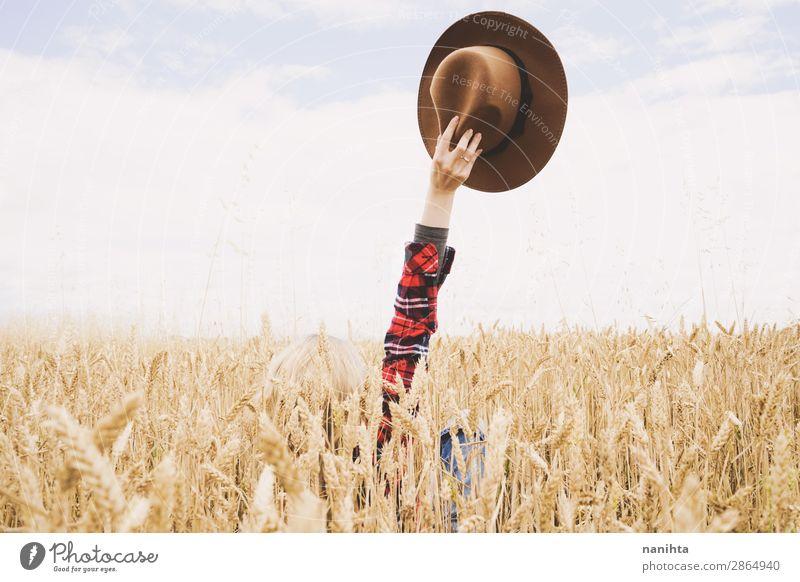 Hand hält einen Cowboyhut über einem Weizenfeld. Bioprodukte Lifestyle Glück schön Wellness Leben Zufriedenheit Erholung Freiheit Sommer Landwirtschaft