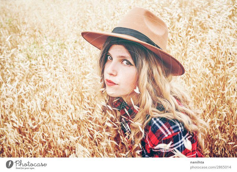 Junge Cowgirl auf einem Getreidefeld Lifestyle Stil schön Wellness Wohlgefühl Sinnesorgane Freiheit Sommer Industrie Mensch feminin Junge Frau Jugendliche