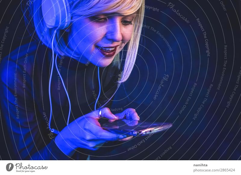 Junge Frau beim Musikhören Lifestyle schön Gesicht Leben Nachtleben Diskjockey Telefon Handy Headset Technik & Technologie Unterhaltungselektronik Fortschritt