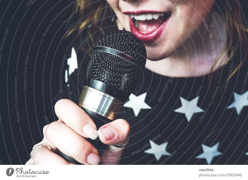 Junge Frau singt ein Lied mit einem Mikrofon. Lifestyle Stil Freude Gesicht Leben Freizeit & Hobby Technik & Technologie Unterhaltungselektronik Mensch feminin