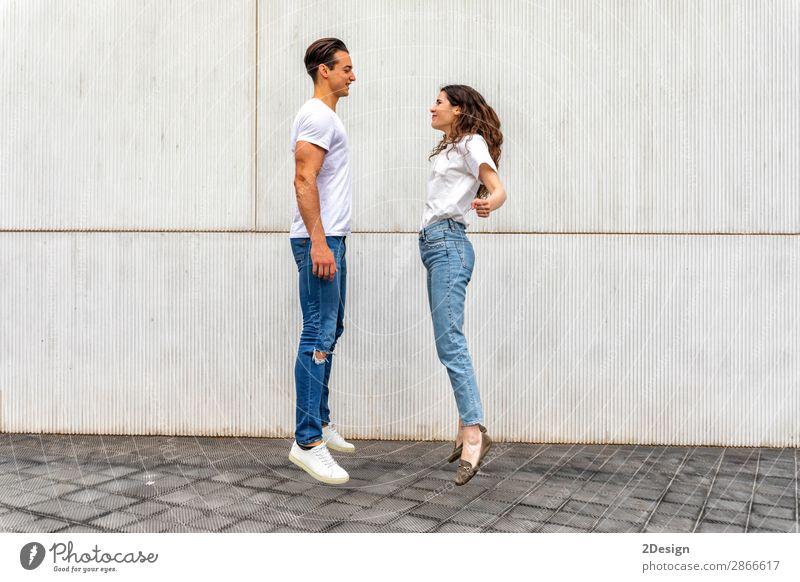 Seitenansicht Glückliches verliebtes Paar, das gegen eine graue Wand springt. Lifestyle Freude Freizeit & Hobby Haus Mensch maskulin feminin Junge Frau