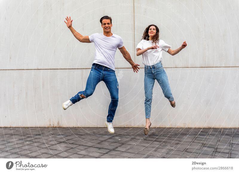 Ein glückliches verliebtes Paar, das gegen eine graue Wand springt. Lifestyle Freude Glück Freizeit & Hobby Haus Mensch maskulin feminin Junge Frau Jugendliche