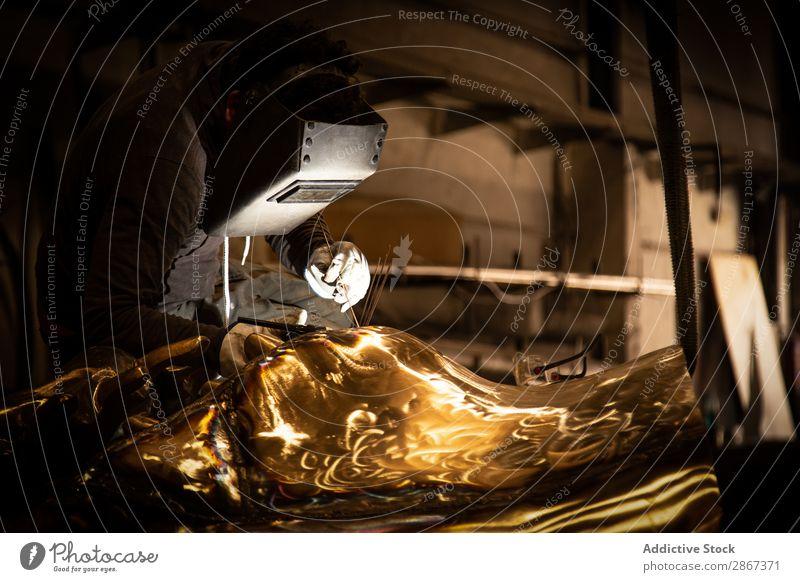 Mann in Maske beim Schweißen von Metallwaren bei Dunkelheit Ware Gießerei Fabrik Kleinunternehmen Werkstatt Helm Produkt klein industriell Produktion Sicherheit