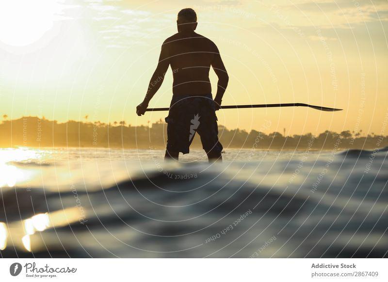Mann mit Paddel auf dem Surfbrett zwischen Wellenwasser bei Sonnenuntergang Wasser Oberfläche Sport Bali Indonesien