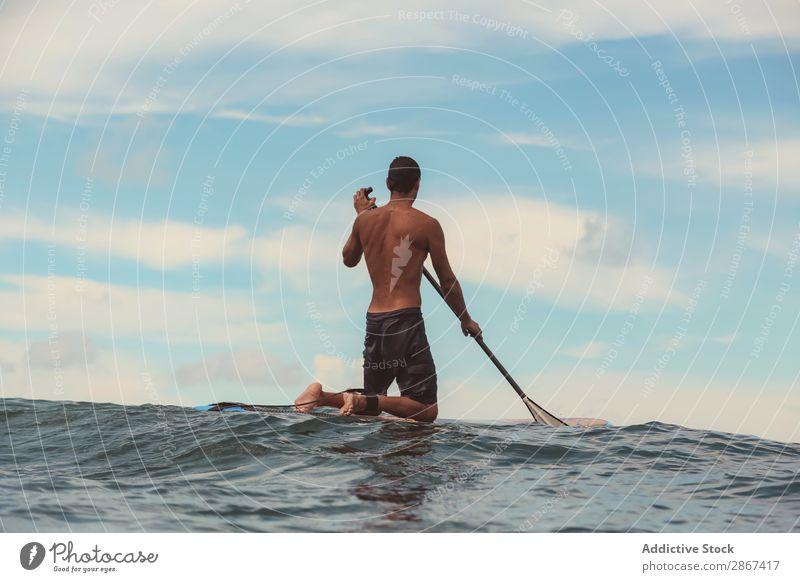 Mann mit Paddel auf dem Surfbrett winkend auf dem Wasser Oberfläche Sport Bali Indonesien