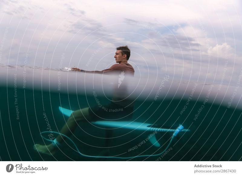Mann sitzt auf dem Surfbrett und schwimmt im blauen Wasser. Sport Bali Indonesien Surfen