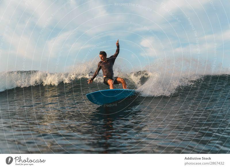 Mann auf dem Surfbrett auf winkendem Wasser Oberfläche Sport Bali Indonesien platschen
