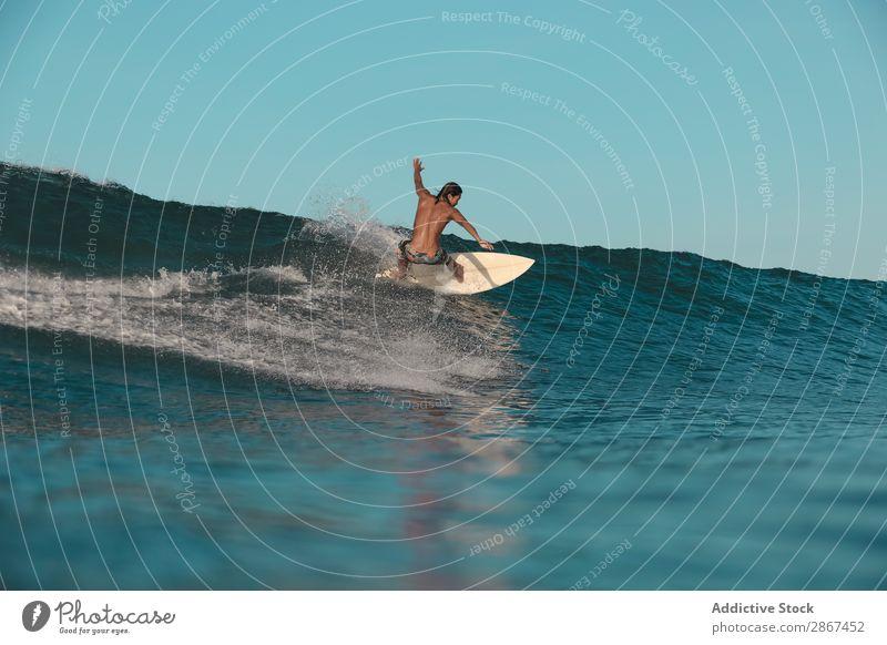 Mann auf dem Surfbrett auf winkendem Wasser bei Sonnenuntergang Oberfläche Sport Bali Indonesien platschen