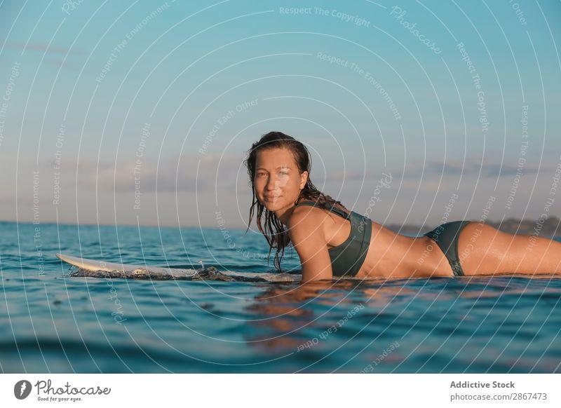 Lächelnde Frau auf dem Surfbrett, die auf dem Wasser schwimmt. Sport Bali Indonesien Surfen winken fliegend blau Meer Oberfläche Himmel (Jenseits) heiter