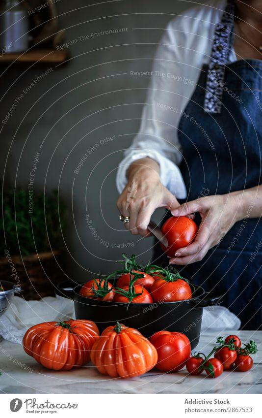 Frau, die Tomaten in einem Topf am Tisch schneidet. Schneiden Gemüse rot reif Messer frisch groß Lebensmittel Dame Mahlzeit rustikal Gesundheit kochen & garen