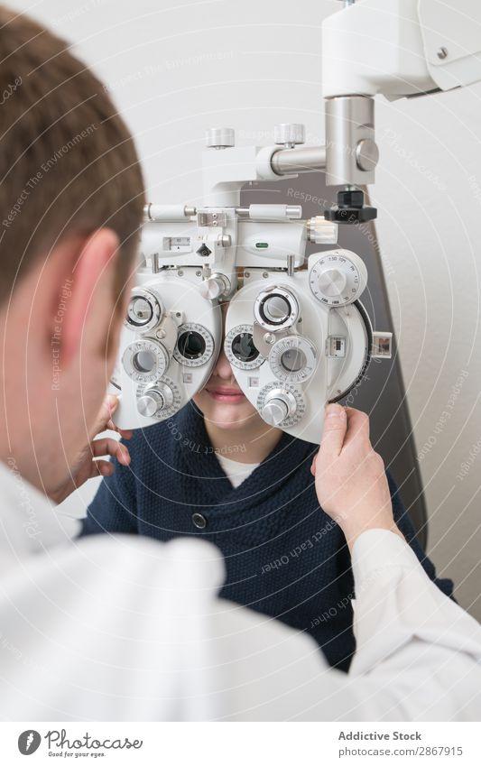 Optiker testet die Augen eines Jungen Kind Klinik Gerät diagnostizieren Anzeige Arzt Prüfung & Examen Brillenträger Gesundheit Krankenhaus Hygiene Medikament