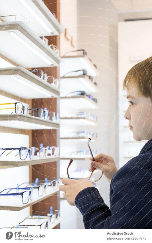 Kleiner Junge beim Anprobieren einer Brille Kind Auge Mode Brillenträger Linse Ophtalmologe Optiker Augenoptikerin Optometrie Blick Sonnenbrille Sehvermögen