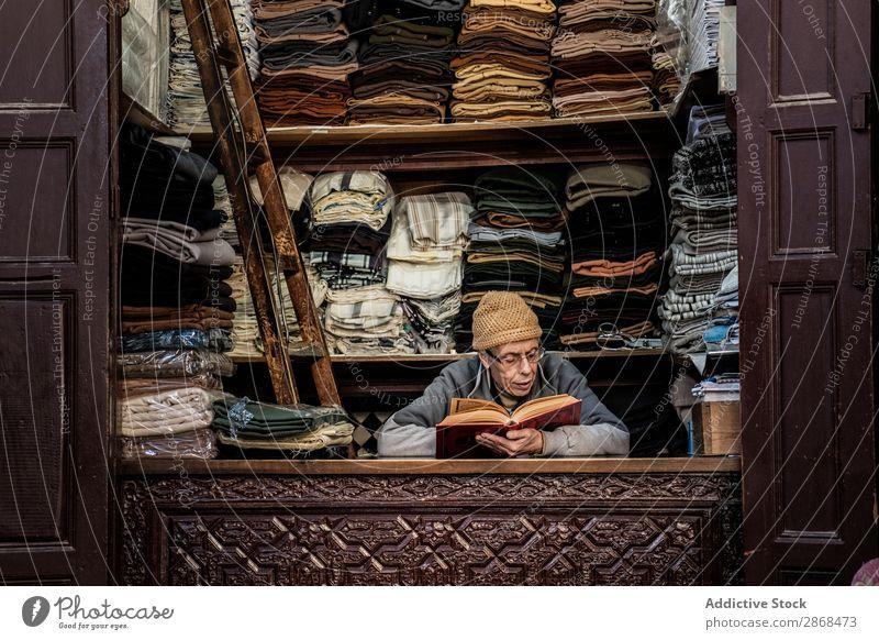 Verkäufer liest Buch am Arbeitsplatz Stoff Markt lesen Roman Bildung Interesse Bekleidung mehrfarbig lokal kaufen Ferien & Urlaub & Reisen