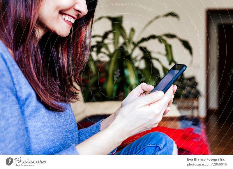 junge Frau, die zu Hause auf dem Sofa sitzt und ein Handy benutzt. Lifestyle Design Arbeit & Erwerbstätigkeit Arbeitsplatz Büro Kapitalwirtschaft Telefon