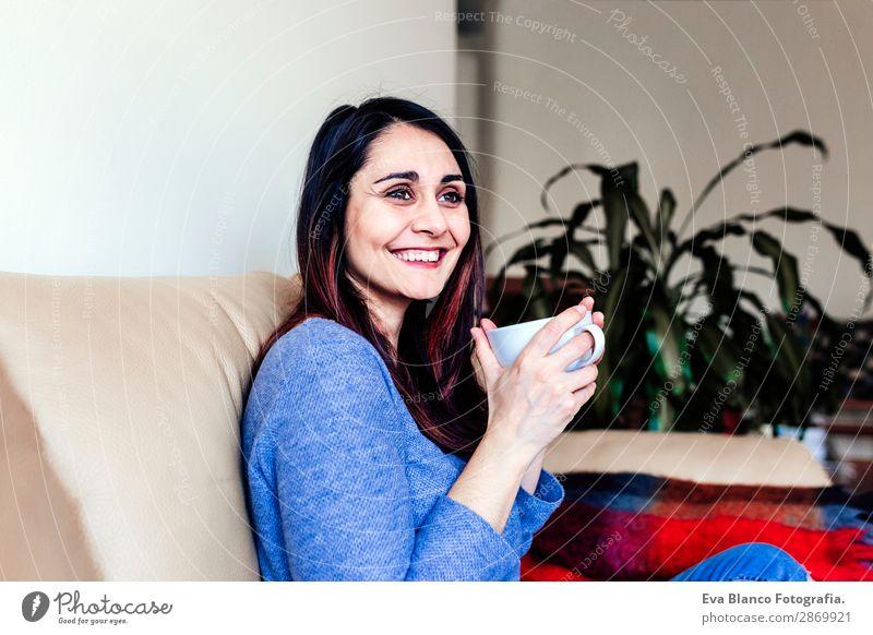 junge kaukasische Frau beim Kaffee zu Hause Frühstück Getränk Tee Lifestyle Glück Freizeit & Hobby Sofa Mensch feminin Junge Frau Jugendliche Erwachsene 1