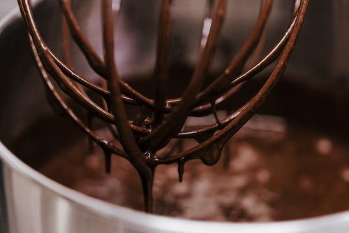 Schokoladenbesen mit eingetauchtem Schneebesen aus nächster Nähe Dessert Küche Werkzeug Metall Stahl Tropfen dreckig weiß Mischung Draht Single Sirup