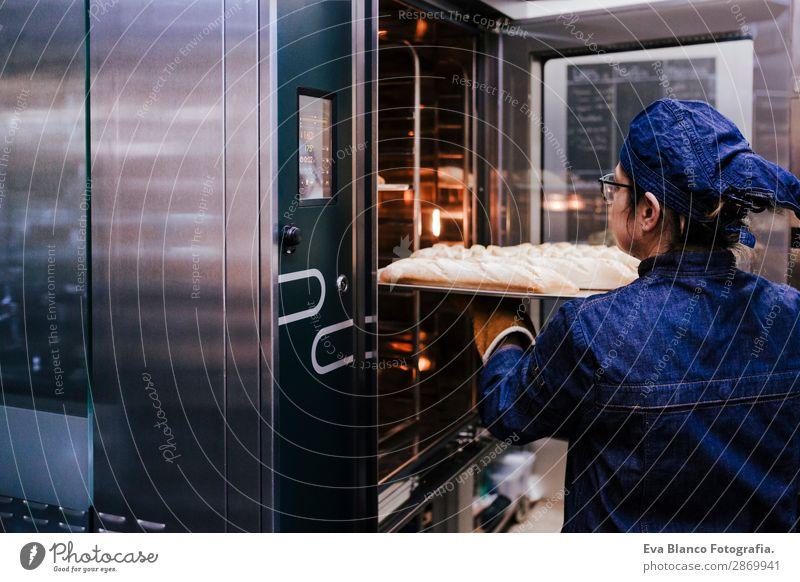 Frau mit einem Brötchenregal in einer Bäckerei. Brot Glück Küche Restaurant Schule Arbeit & Erwerbstätigkeit Beruf Fotokamera feminin Erwachsene 1 Mensch