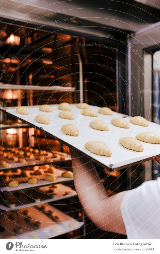 Frau, die ein Regal mit Croissants in einer Bäckerei hält. Brot Glück Küche Restaurant Schule Arbeit & Erwerbstätigkeit Beruf Fotokamera feminin Erwachsene Hand