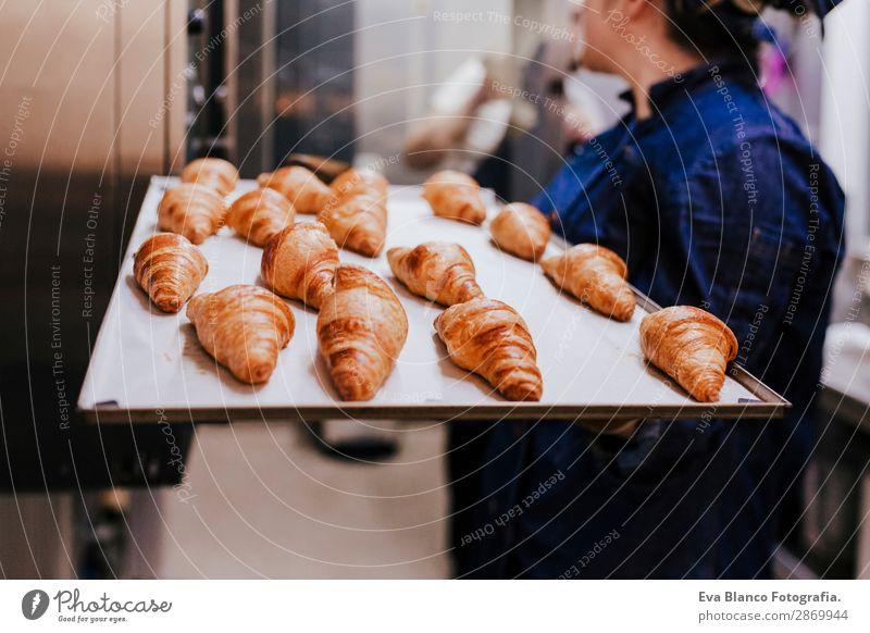 Frau hält ein Regal mit Croissants in einer Bäckerei. Brot Glück Küche Restaurant Schule Arbeit & Erwerbstätigkeit Beruf Fotokamera feminin Erwachsene 1 Mensch