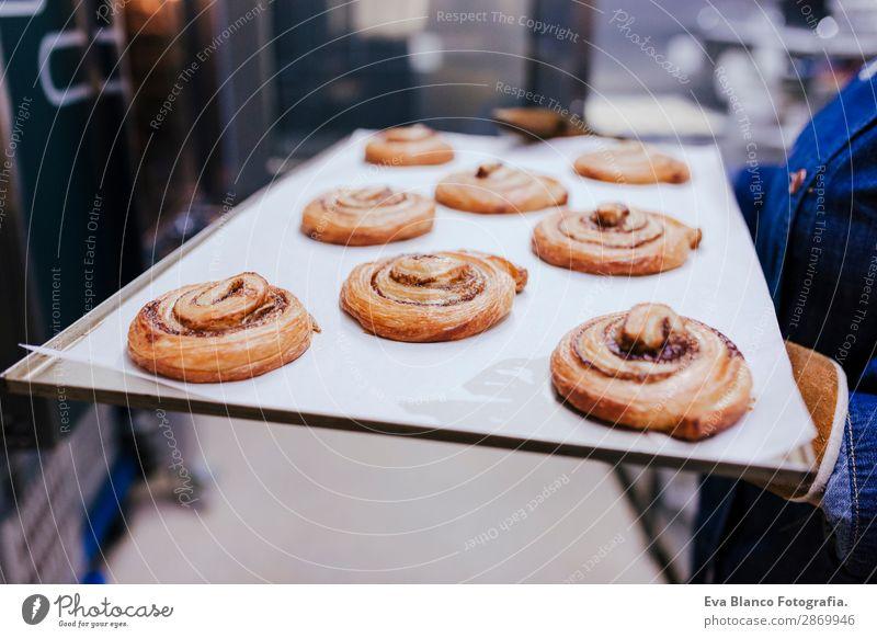 Frau hält ein Regal mit Süßigkeiten in einer Bäckerei. Brot Glück Küche Restaurant Schule Arbeit & Erwerbstätigkeit Beruf Fotokamera Erwachsene Gebäude
