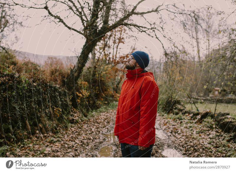 Ein Junge in einem roten Mantel ist auf einer Schlammstraße. Lifestyle Glück Erholung Freizeit & Hobby Ferien & Urlaub & Reisen Abenteuer wandern Sport