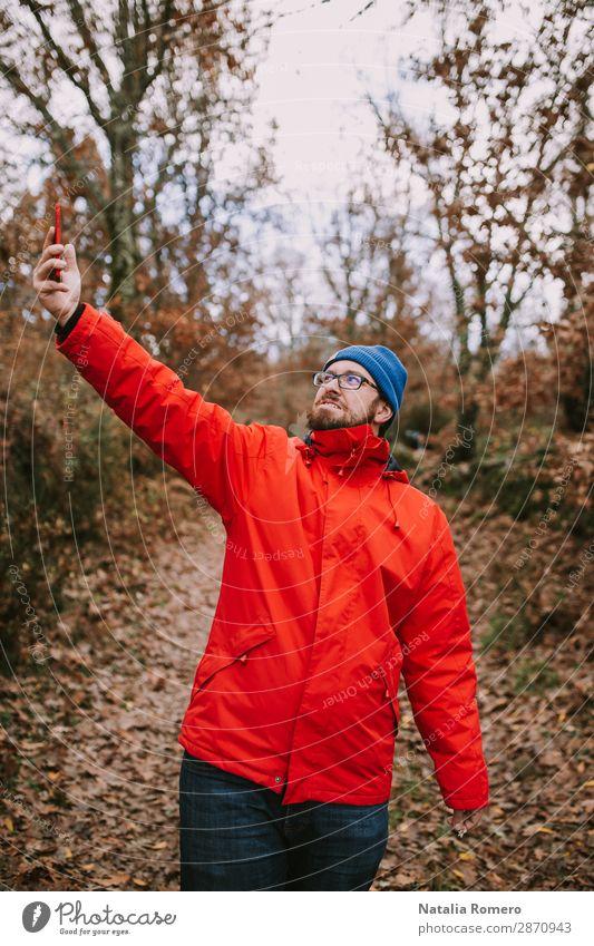 Junger Mann mitten im Wald sucht nach Deckung. Lifestyle schön Ferien & Urlaub & Reisen Abenteuer wandern Telefon Bildschirm Technik & Technologie Mensch