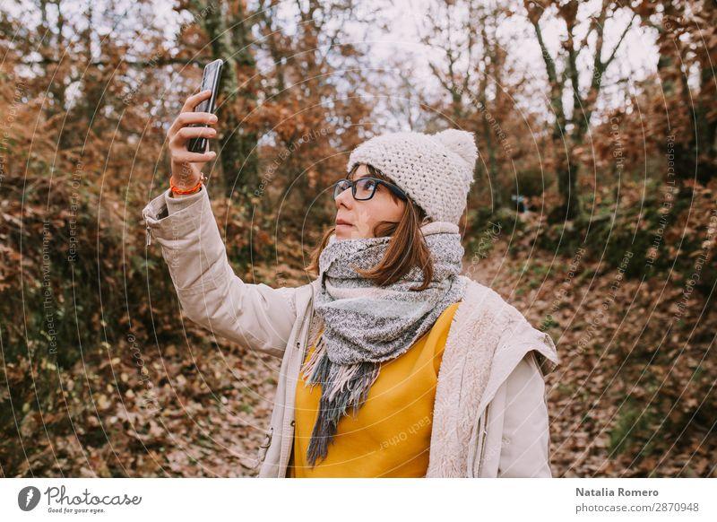 eine junge Frau schaut auf das Handy im Wald. Lifestyle schön Ferien & Urlaub & Reisen Abenteuer wandern Telefon Bildschirm Technik & Technologie Mensch