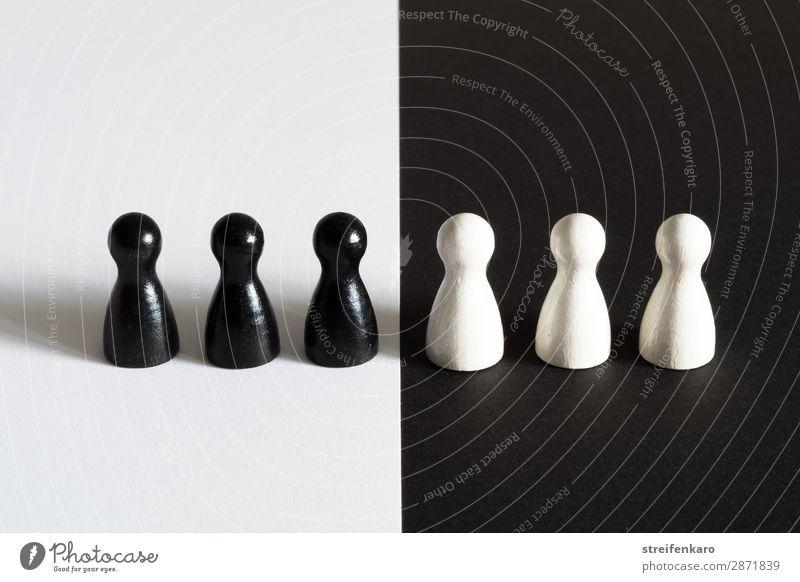 Schwarze Spielfiguren auf weißem Untergrund stehen weißen Spielfiguren auf schwarzem Untergrund gegenüber Menschengruppe Spielzeug Holz beobachten Akzeptanz