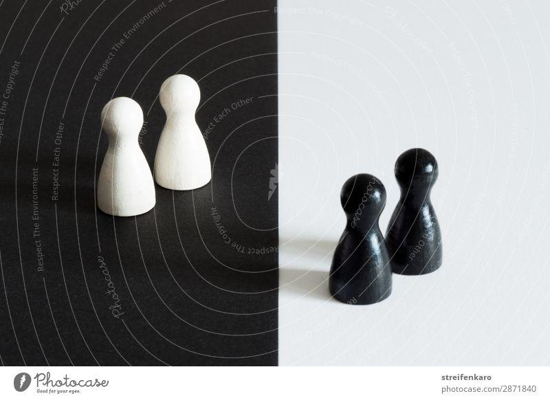 Zwei weiße Spielfiguren auf schwarzem Untergrund stehen zwei schwarzen Spielfiguren auf weißem Untergrund gegenüber Menschengruppe Spielzeug Holz Zeichen