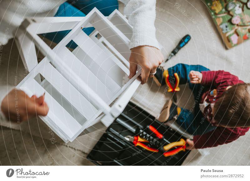 Frau, die Möbel zu Hause mit der Tochter zusammenbaut. Lifestyle heimwerken Umzug (Wohnungswechsel) einrichten Innenarchitektur Dekoration & Verzierung Mensch
