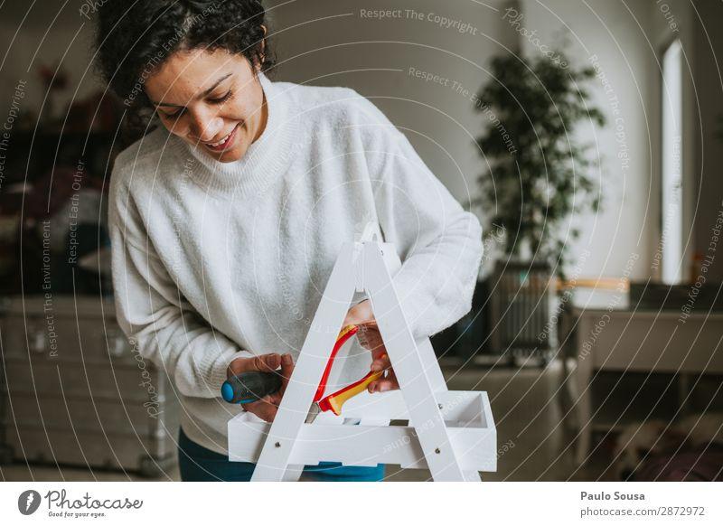 Frau, die Möbel zu Hause zusammenbaut. Lifestyle einrichten Innenarchitektur feminin Erwachsene 1 Mensch 18-30 Jahre Jugendliche Dekoration & Verzierung Holz