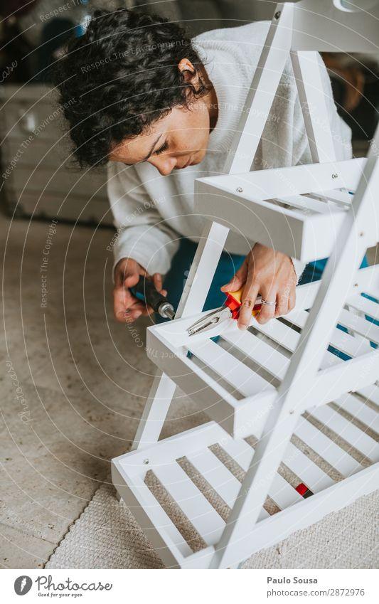 Frau, die Möbel zu Hause zusammenbaut. Lifestyle einrichten Mensch feminin Junge Frau Jugendliche 1 18-30 Jahre Erwachsene Erfolg modern weiß selbstbewußt