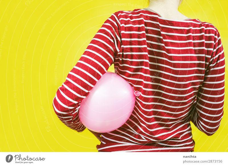 Rückansicht eines Mädchens, das einen Ballon hält. Stil Design Feste & Feiern Geburtstag Kind Frau Erwachsene Kindheit Kunst Hemd Luftballon Streifen