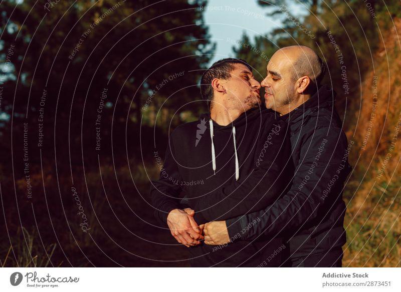 Lächelnde Männer, die sich auf dem Weg im Park umarmen. Homosexualität Paar Umarmen Liebe Wege & Pfade Wald umarmend Schönes Wetter geschlossene Augen heiter