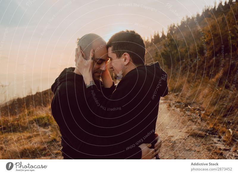 Männer, die sich im Wald umarmen und küssen. Homosexualität Paar Park Küssen Liebe Händchenhalten Wege & Pfade Schönes Wetter geschlossene Augen Sonne Natur