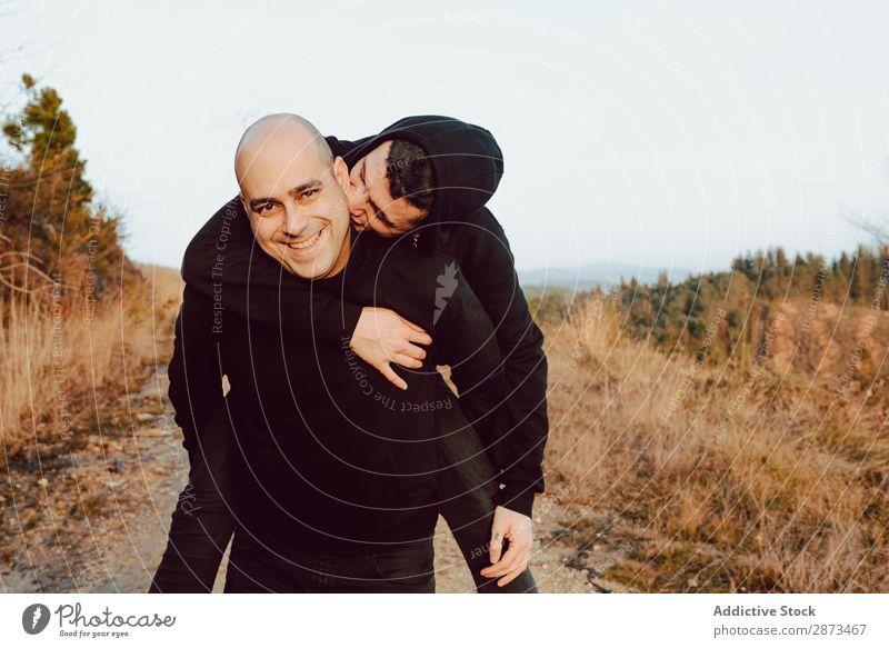 Lächelnder Mann, der den fröhlichen Kerl auf der Straße auf dem Hügel zurückhält. Homosexualität Paar Umarmen Rücken Spaß haben Liebe umarmend Berge u. Gebirge
