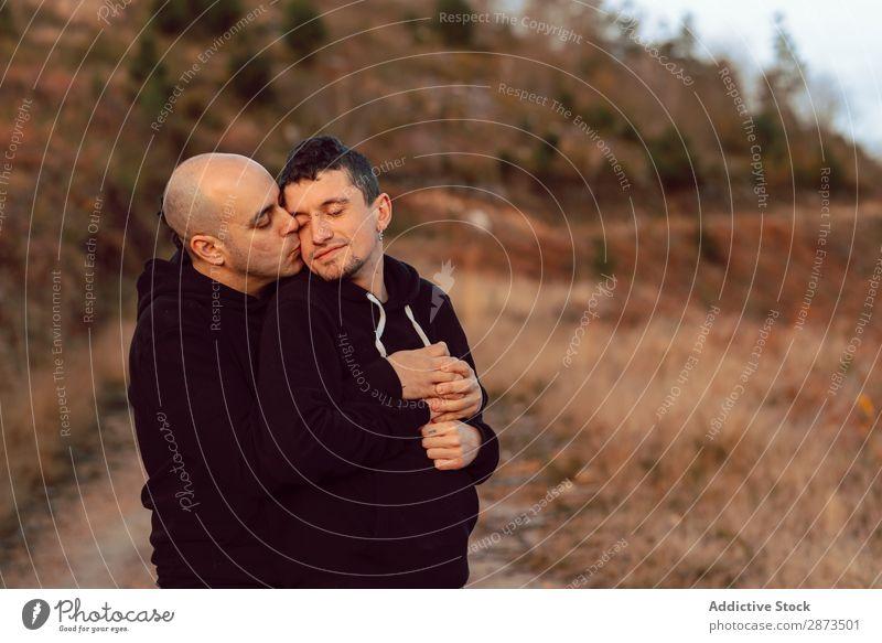 Männer, die sich auf der Straße am Berg umarmen. Homosexualität Paar Umarmen Hügel Silhouette Tal Liebe umarmend malerisch Aussicht Nebel Berge u. Gebirge