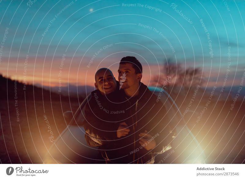Männer, die sich nachts auf dem Feld in der Nähe des Autos umarmen. Homosexualität Paar PKW Umarmen Nacht Landschaft Liebe umarmend Glück Scheinwerfer Natur