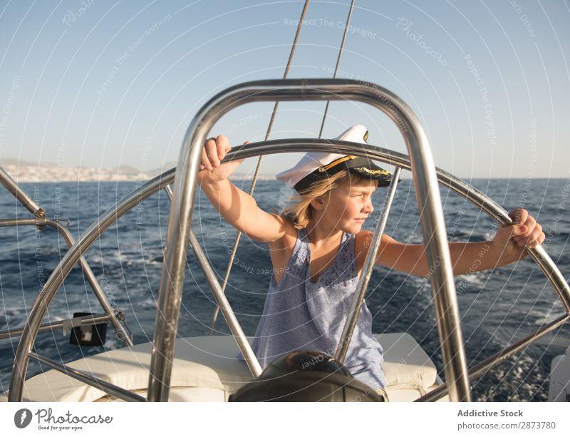 Lächelndes Mädchen hält das Lenkrad auf der Yacht auf dem Wasser. Jacht Kapitän Hut Meer Kind fliegend Schönes Wetter Wasserfahrzeug teuer aussruhen positiv