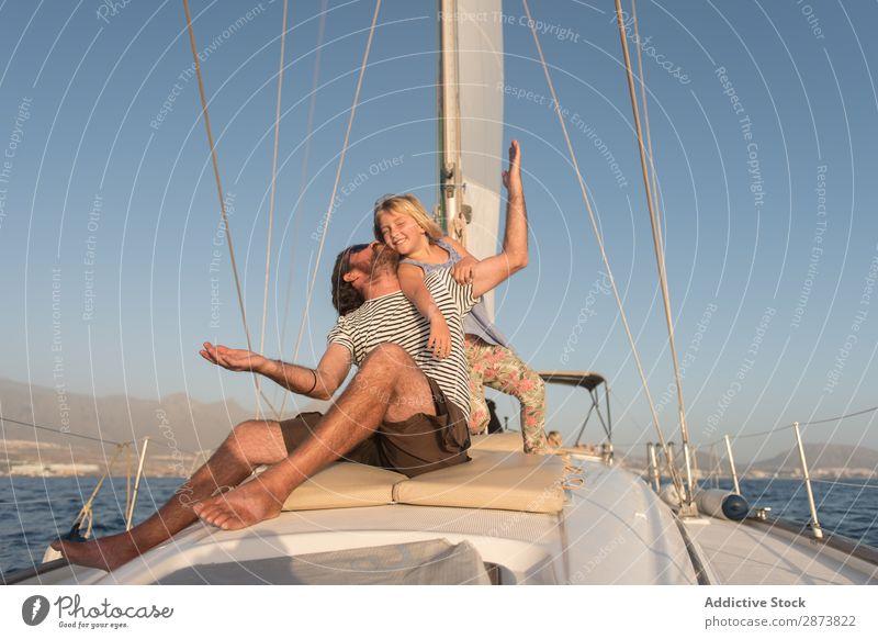 Mann hat Spaß mit lächelndem Mädchen und sitzt auf dem Deck einer Yacht im Meer. Jacht Vater Kind fliegend Wasserfahrzeug Tochter Schiffsdeck Spaß haben