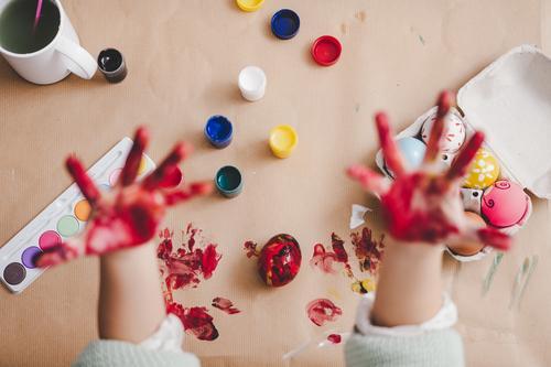 Kind zeigt schmutzige Hände in der Nähe von Hühnereiern und Farben am Tisch. Hand Ostern Ei dreckig zeigen malen Handfläche Hähnchen Container Frühling Kulisse