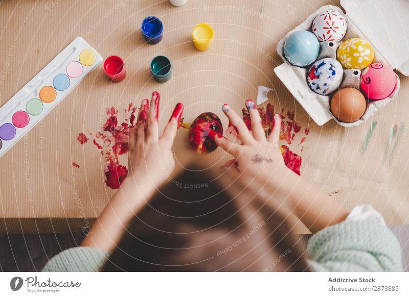 Kind mit schmutzigen Händen in der Nähe von Hühnereiern und Farben am Tisch. Hand Ostern Ei dreckig malen Handfläche Hähnchen Container Frühling Kulisse