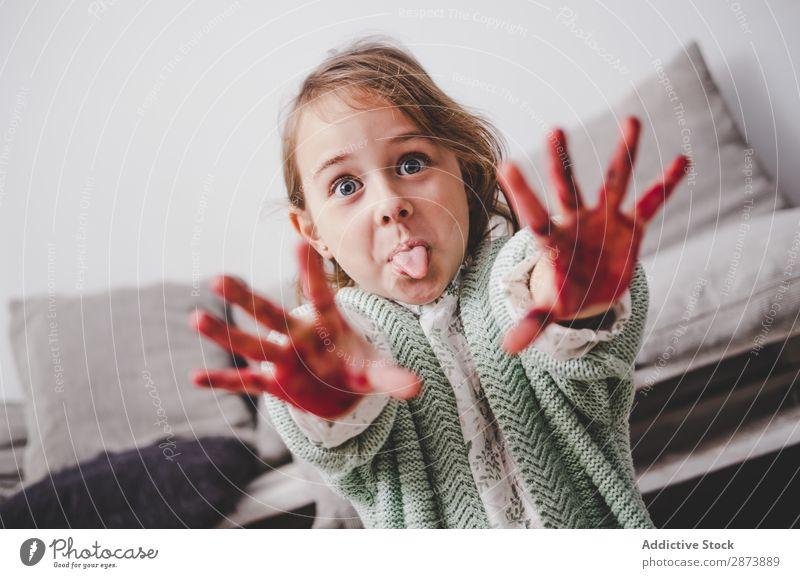 Mädchen mit schmutzigen Händen, die die Zunge im Raum zeigen. Hand dreckig Farbe konfrontierend Sofa malen lustig Kind Dekoration & Verzierung mehrfarbig hell