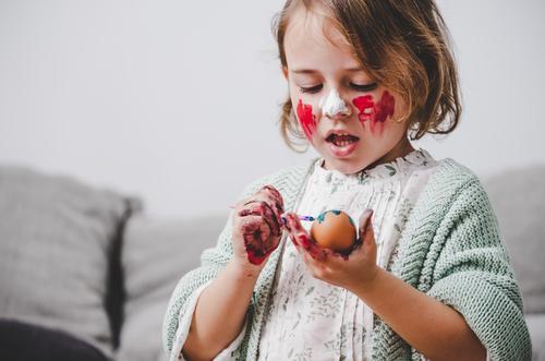 Mädchen mit Pinsel färbt Hühnereier am Tisch im Zimmer. Ostern Ei Bürste Raum Sofa Färbung lustig Kind Hähnchen Container Gemälde Frühling Kulisse