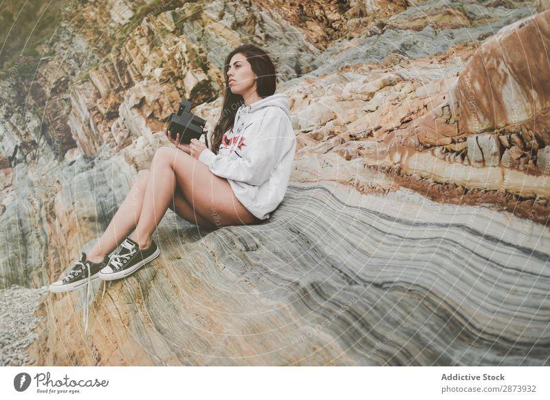 Dame mit Kamera an Land in der Nähe von Steinen und Wasser Frau Küste Meer Fotokamera heiter retro Jugendliche Lifestyle laufen Unterwäsche Pullover Felsen