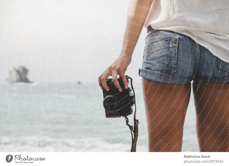 Dame mit Kamera an Land in der Nähe von Steinen und Wasser Frau Fotokamera Küste Meer Jugendliche