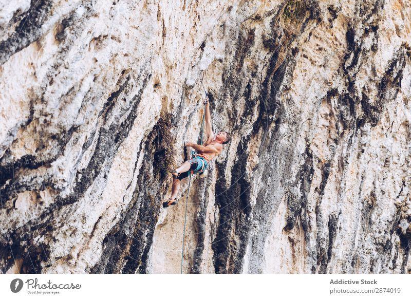 Anonymer Mann klettert auf den Felsen Klettern Klippe extrem Sport Herausforderung Aktion Erfolg Kraft Höhe erhängen Seil Abenteuer Risiko sichern