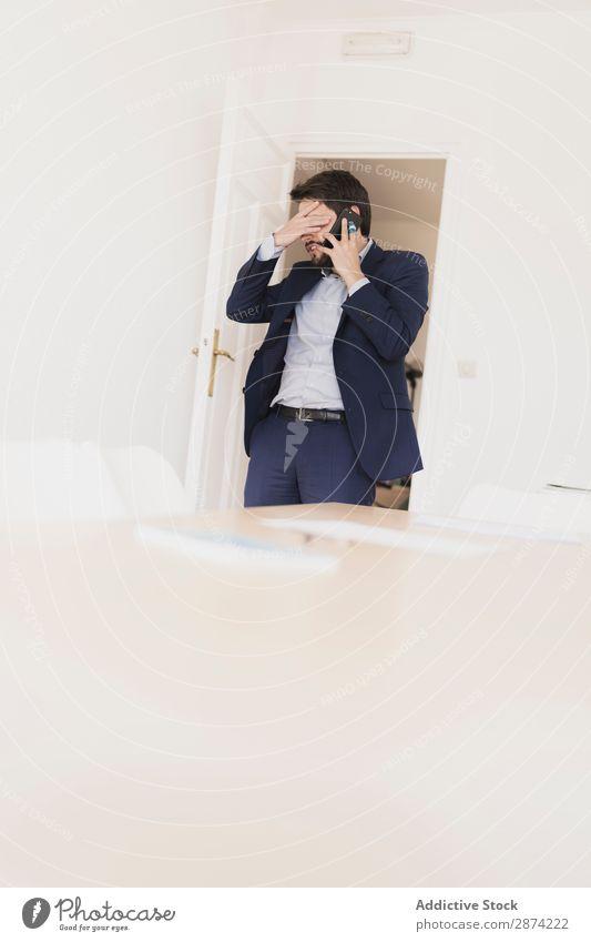 Ernsthafter Mann im Gespräch auf dem Smartphone im Raum neben den Stühlen PDA sprechen Stuhl Hand Tasche Aktion Tisch Arbeit & Erwerbstätigkeit konzentriert