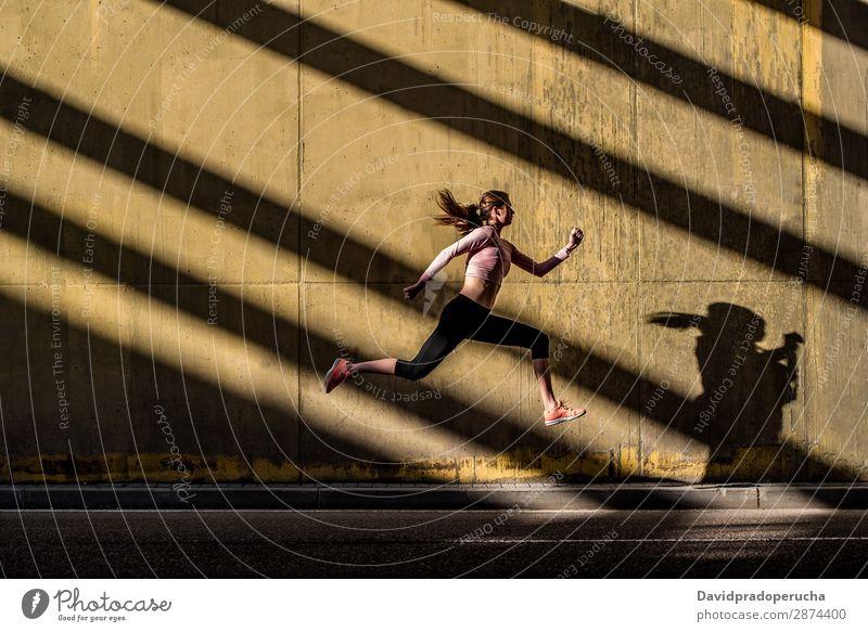 Junge, fitte, blonde Frau, die auf der Straße springt. springen rennen üben Fitness ausarbeiten Lifestyle Bewegung Aktion Joggen Profil horizontal sportlich